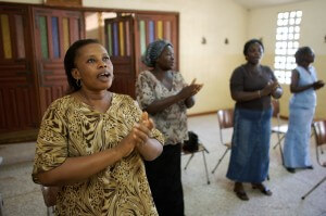 Opportunity Ghana client Mary Donkor sings in praise at devotions before a Trust Group meeting at the Blessed Mary Church in Accra.