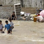 A river crossing as others clean belongings after floods receded on Saturday in suburban Montalban, east of Manila. (AP)