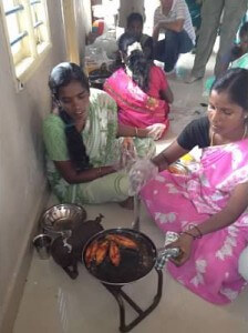 Women in the Trust Group fry seer fish with the travelers.