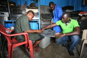 Edward (right) repairs sound systems with his employees.