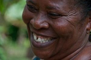 Opportunity Ghana client Beatrice Boaten smiles while standing at her farm. (Photo: Sara Joe Wolansky)