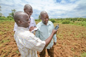 Asuman, left, measures his fields with a GPS device and help from Regional Agricultural Supervisor John Peter Emoi, center, and fellow farmer Joseph Mulandya.