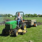 International Business Development's Mary clears brush with the tractor.