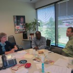 Staff members Steve Nelson (right) and Michael Okleme (center) visit with volunteer Linda.