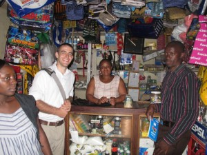 In the largest market in Moshi - AJ and a client (behind the counter) and her loan officer (at right).