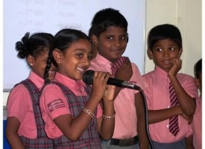 Ramya, a scholarship recipient, takes the mike to introduce herself to Insight Trip travelers when they visit her school.