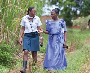 Opportunity Relationship Officer Phiona Ndikibuliraani, left, offers guidance to sugarcane farmer Loy Naigaga, in rural Uganda, ensuring Joy's long-term financial success.