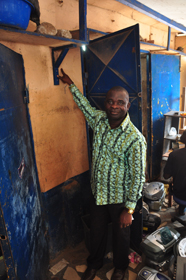 James Aby Kwame Prah, a MicroEnsure Ghana client, shows the water level in his Accra shop after last year's floods. MicroEnsure's insurance is helping him rebuild his shop.