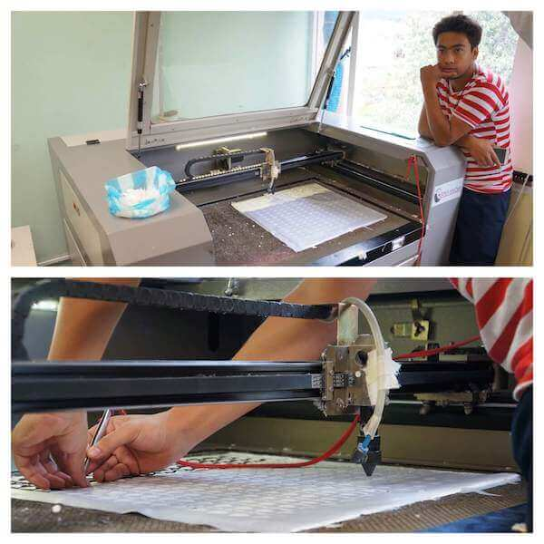 Luz's son operating the laser cutter