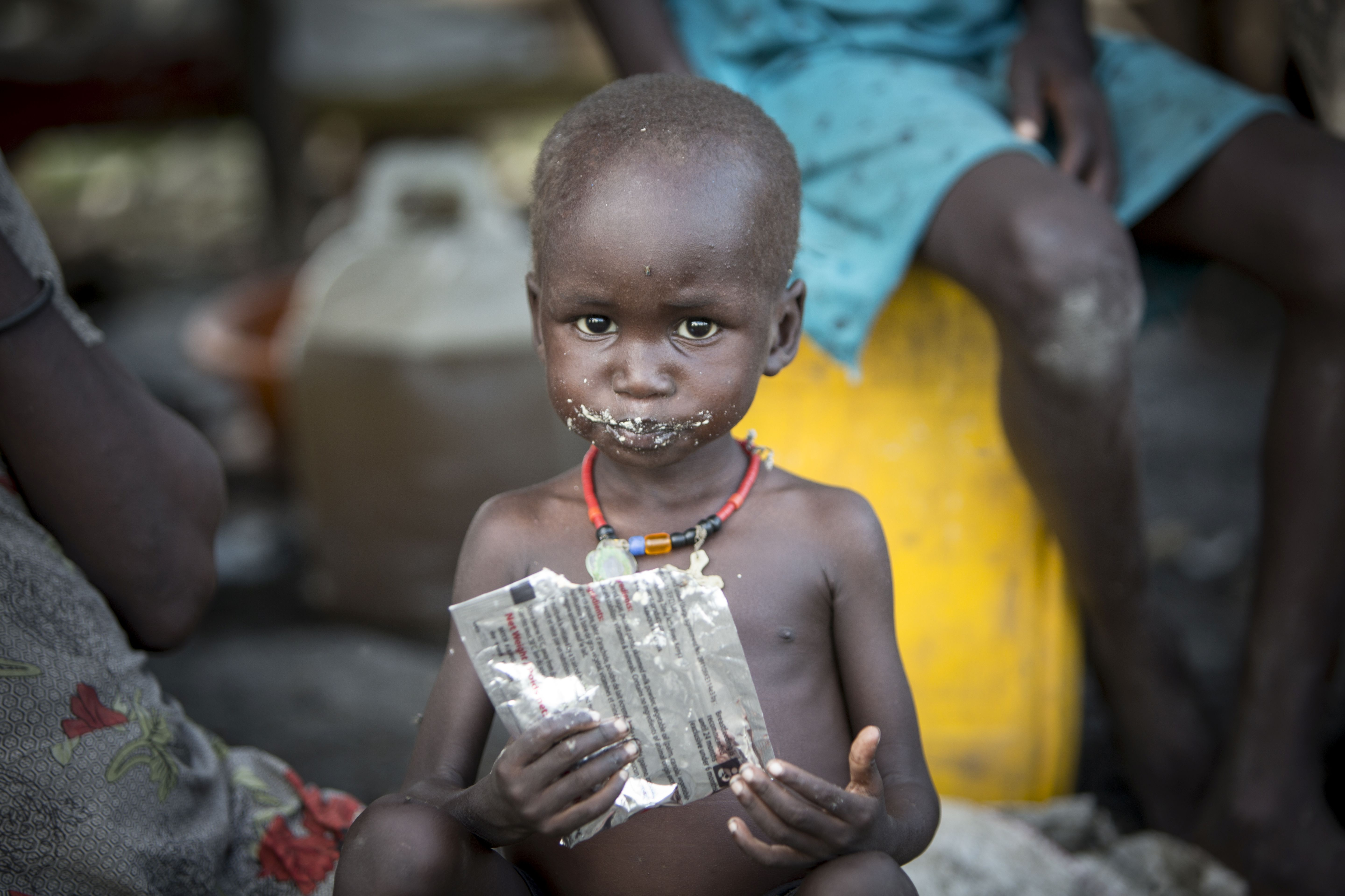 Small dark skinned boy looking into the camera, with a face covered in powder from the small amount of food he had eaten